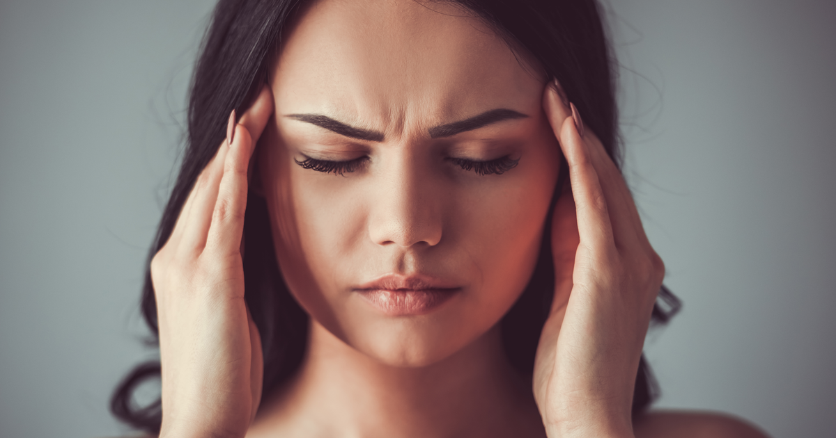 Woman with stress headache applies pressure to pressure points for instant headache relief.