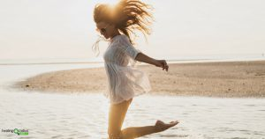 Young woman on the beach leaping for success and happiness