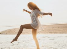 Successful young woman happily dancing on the shore